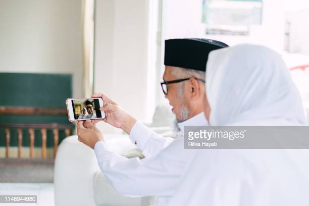 senior adult taking selfie with mobile phone for eid mubarak - eid mubarak stock pictures, royalty-free photos & images
