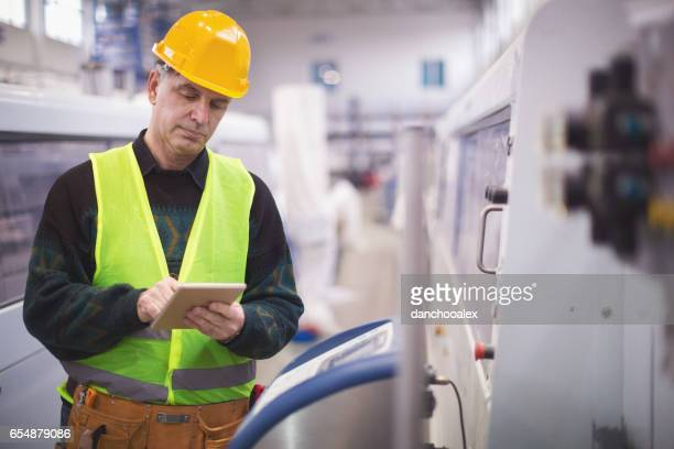 Senior adult using tablet pc in factory
