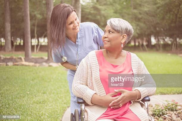 Persona mayor con su personal de enfermería de atención médica, cuidador al aire libre. Hogar para silla de ruedas.