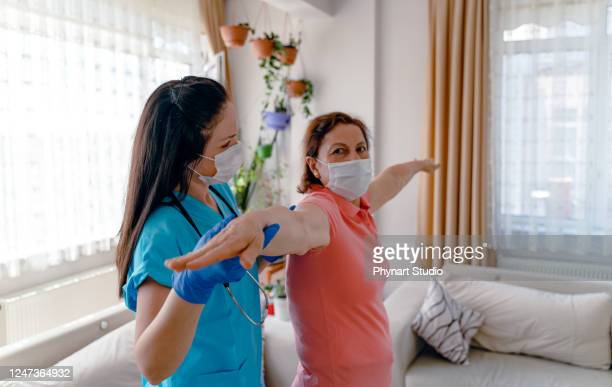 idosa adulta e enfermeira de saúde domiciliar, fisioterapeuta. - recuperação - fotografias e filmes do acervo