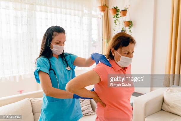 senior adult woman and home healthcare nurse, physical therapist. - rheumatoid arthritis stock pictures, royalty-free photos & images