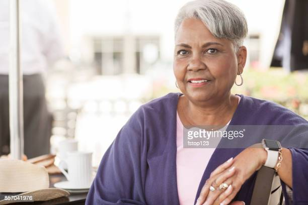 senior adult woman dining at outdoor cafe. - minority groups stock pictures, royalty-free photos & images