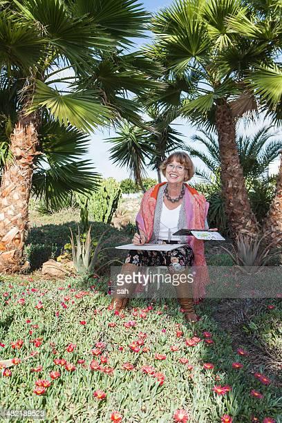Senior adult woman drawing in garden