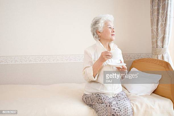 A Senior Adult Woman Drinking Coffee on Bed