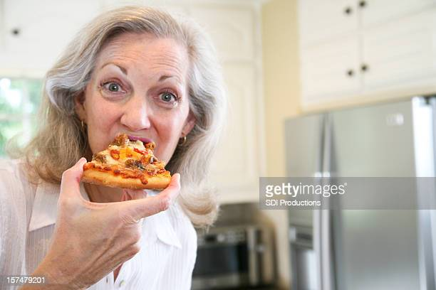 senior adult woman eating a delicious pizza - alleen één seniore vrouw stockfoto's en -beelden