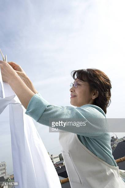a senior adult woman hanging out the laundry under the sky, side view, low angle view - 乾かす ストックフォトと画像