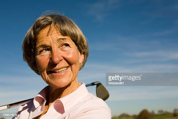 Senior woman holding golf club, smiling, close-up