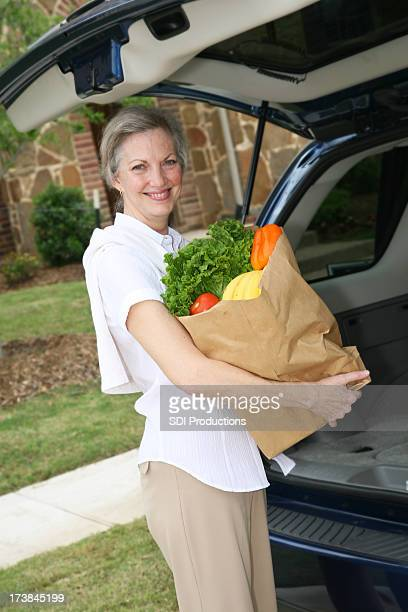 Senior Adult Woman Holding Grocery Bag Outside of Car