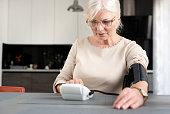 Senior adult woman measuring blood pressure