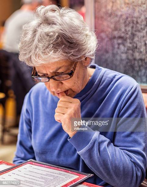 Senior Adult Woman Reading Breakfast Menu at Restaurant