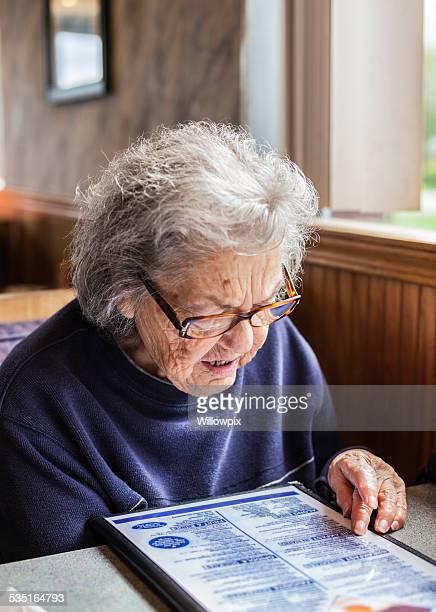 Senior Adult Woman Reading Breakfast Menu in Restaurant