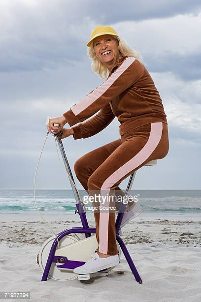 Senior adult woman riding an exercise bike