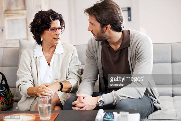 senior adult woman talking to her son. - mother and son stock photos and pictures
