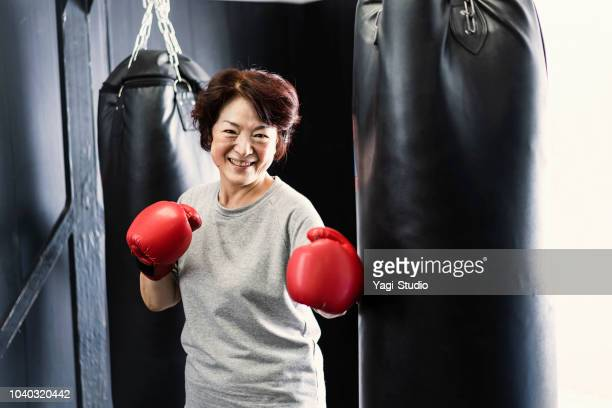 senior adult woman training at boxing gym - punching stock pictures, royalty-free photos & images
