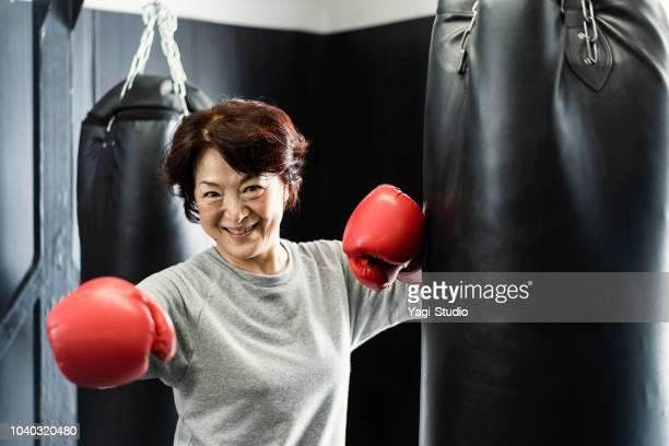 Senior adult woman training at boxing gym