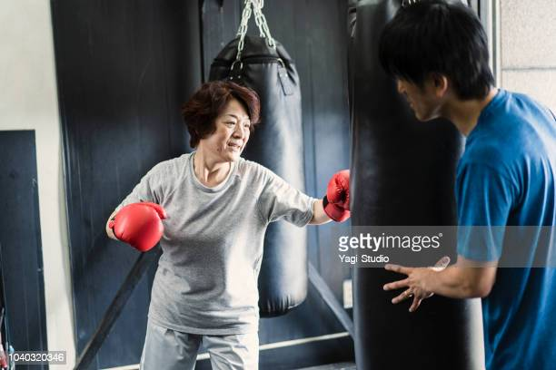Senior adult woman training at boxing gym with coach