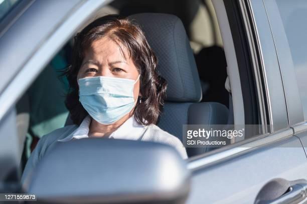 保護マスクを着用したシニアアダルト女性が車の窓の外を見る - ドライブスルー検査 ストックフォトと画像