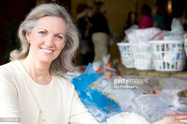 senior adult woman with baskets of groceries at donation center - meals on wheels stock pictures, royalty-free photos & images