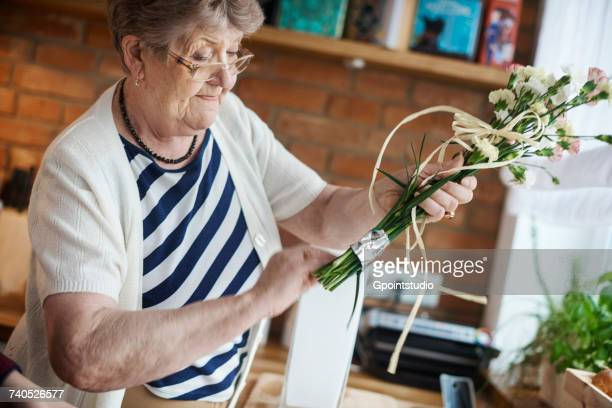 Senior adult woman with floral craftwork