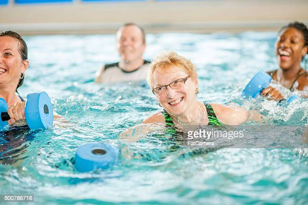 senior adult woman working out in the pool - splashing stock pictures, royalty-free photos & images