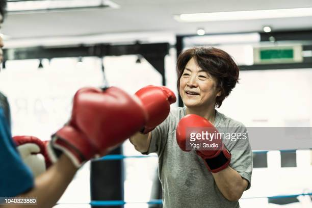 Senior adult women training with male instructor at boxing gym