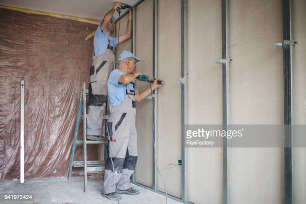 senior adult worker drilling holes on consturction site - foundation make up stock pictures, royalty-free photos & images