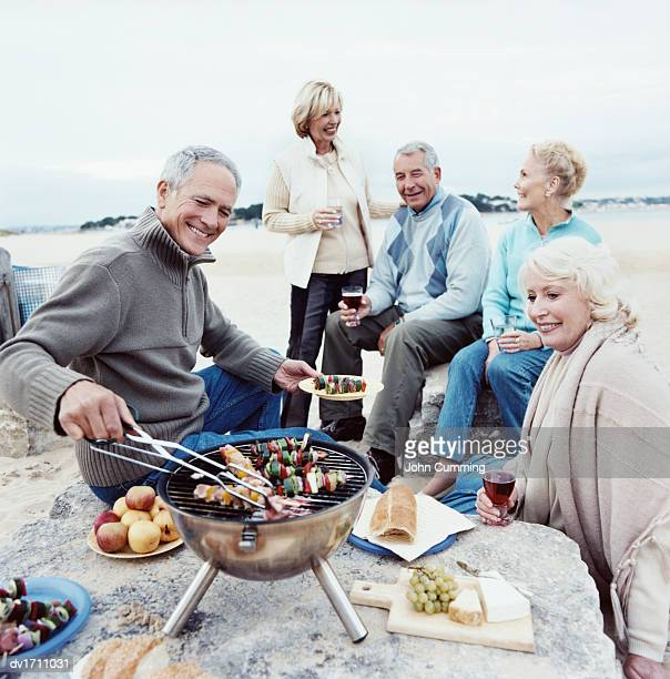 Senior Adults Enjoying a Barbecue on a Beach