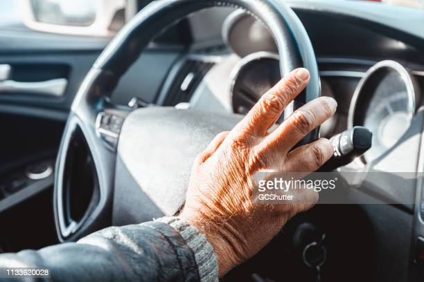 senior adult's hand on the steering wheel - old beirut stock photos and pictures