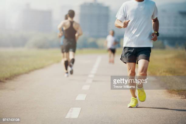 senior adults jogging or running in the park - 走る ストックフォトと画像