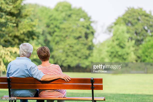 Senior adults outdoors in the park on park bench