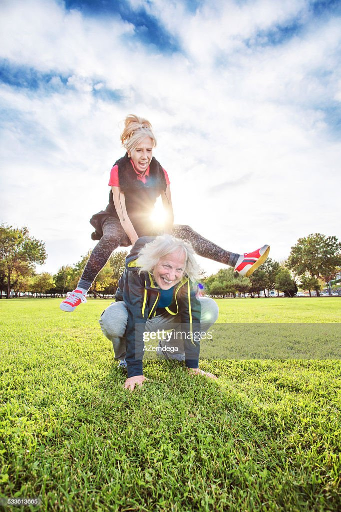 Senior adults playing leapfrog : Stock Photo
