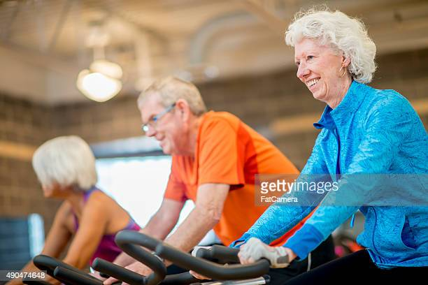 senior adults taking exercise class - circuit training stock photos and pictures