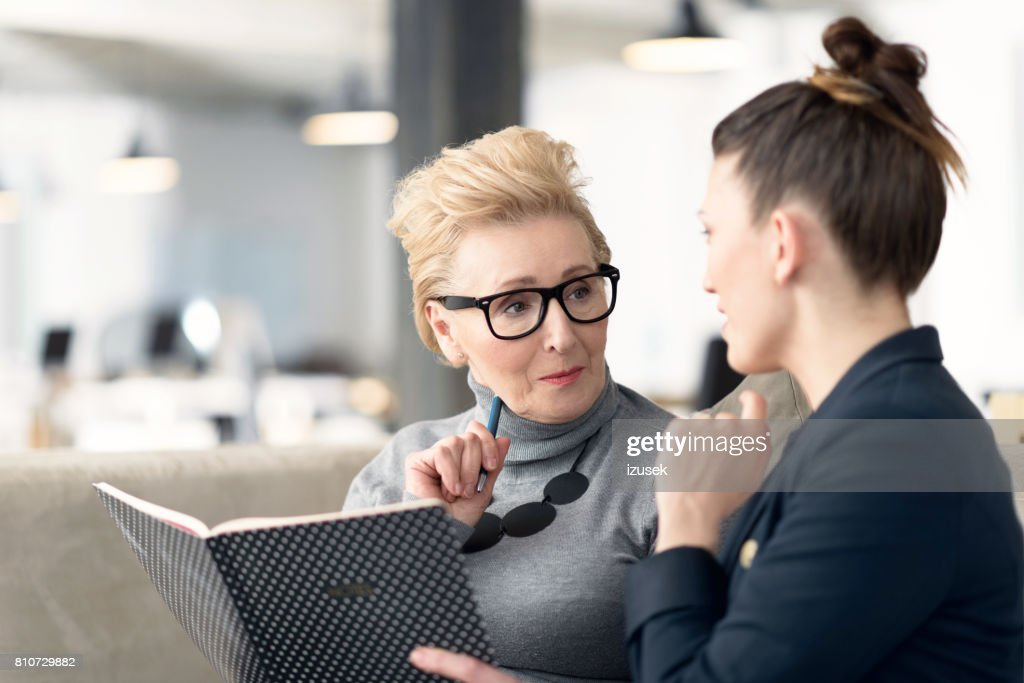 Senior adviser talking with young businesswoman : Stock Photo