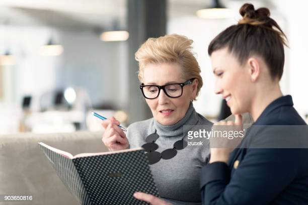 senior adviser talking with young businesswoman - coach stock pictures, royalty-free photos & images