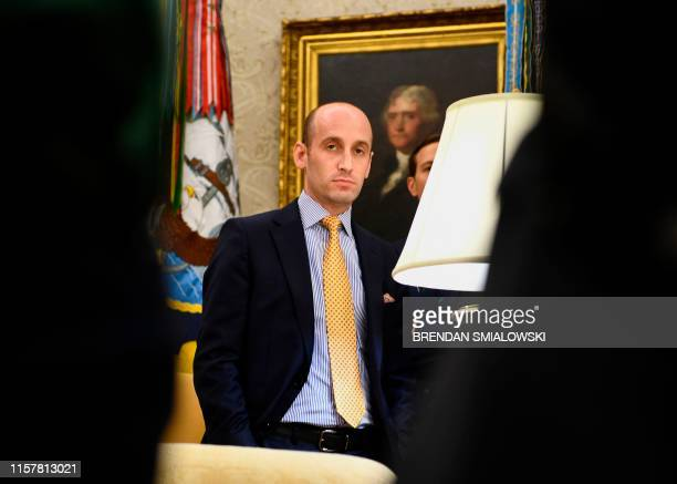 Senior Advisor Stephen Miller looks on as US President Donald Trump speaks to the media in the Oval Office of the White House in Washington DC on...