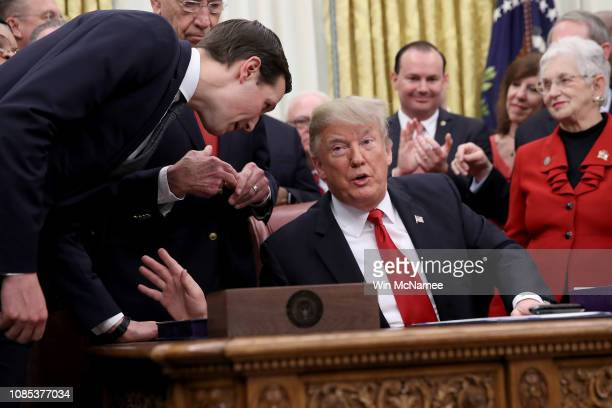 Senior advisor to the President Jared Kushner leans in to speak with US President Donald Trump during the signing ceremony for the First Step Act and...