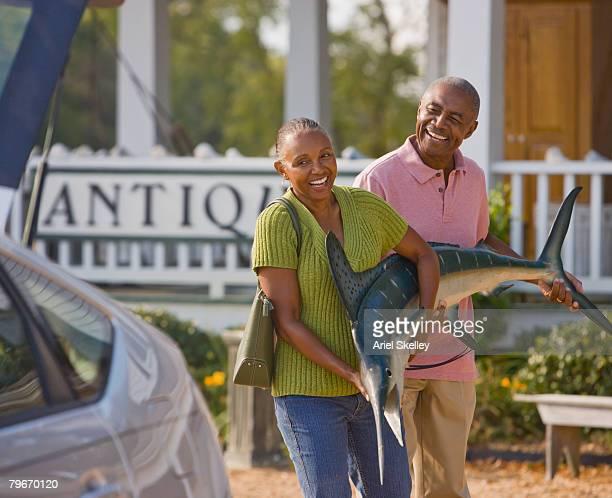 Senior African American couple carrying swordfish