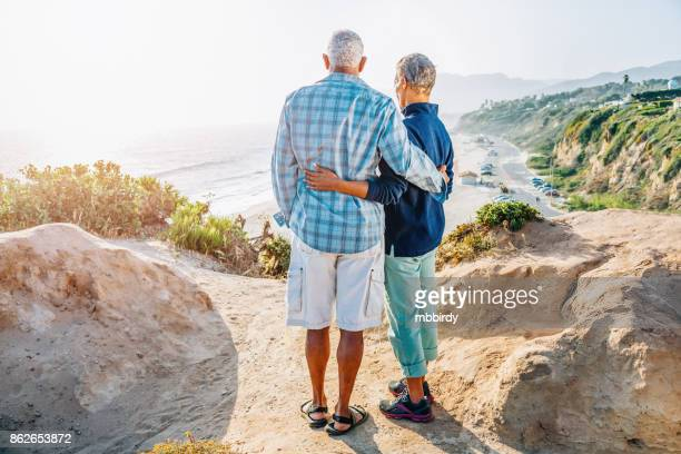 Senior African American couple embracing on rock over beach
