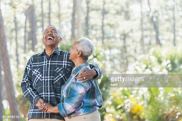 senior african american couple holding hands in park - black people having fun stock photos and pictures