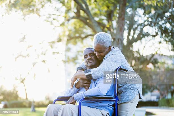 senior african american couple, man in wheelchair - aaien stockfoto's en -beelden