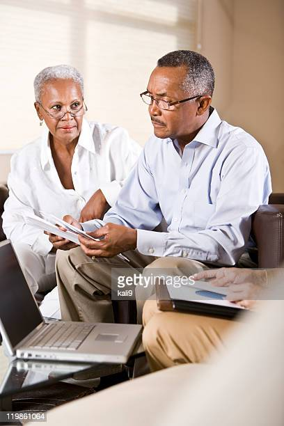 Senior African American couple meeting with financial adviser