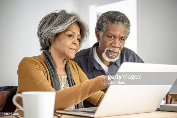 Senior African American couple on laptop together with serious expression
