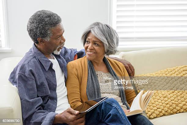 Senior African American couple on sofa smiling affectionately