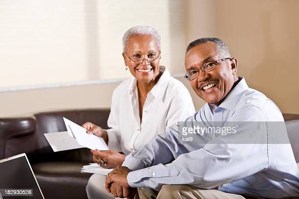Senior African American couple paying bills online