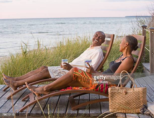 Senior African American couple relaxing in lounge chairs