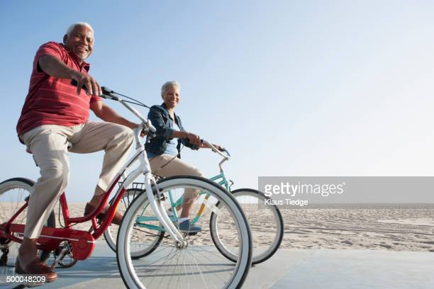 Senior African American couple riding bicycles by beach