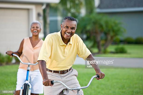 Senior African American couple riding bicycles, focus on man