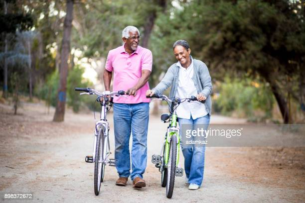 senior african american couple riding bikes - bicycle trail outdoor sports stock photos and pictures