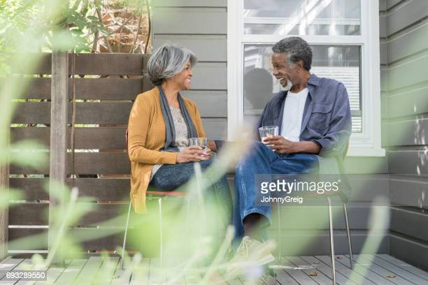 Senior African American couple sitting in garden with drinks