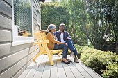 Senior African American couple sitting on porch outside house